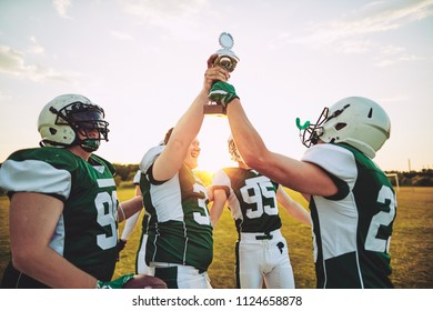 Excited group of young American football players raising a championship trophy together in celebration after a game