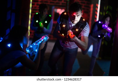 Excited guy aiming laser gun at other players during lasertag game in dark room