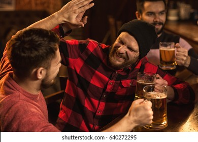 Excited handsome bearded guy having beer with his friend giving him high five celebrating victory winning evening holidays restaurant friendship men guys masculinity bachelor party happiness drinking