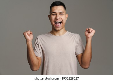 Excited handsome guy exclaiming and making winner gesture isolated over grey background