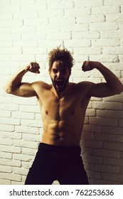 Excited handsome man or bodybuilder, sexy, young, blond, bearded, athlete, male model with beard shouts and shows muscular torso, abs, biceps, triceps on white brick wall