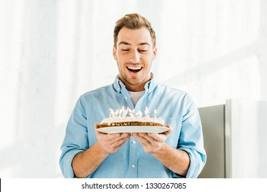 excited handsome man holding birthday cake with burning candles at home in morning