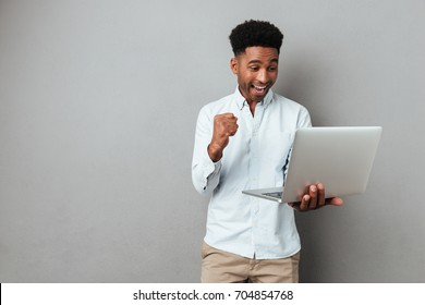 Excited happy afro american man looking at laptop computer screen and celebrating the win isolated over gray background