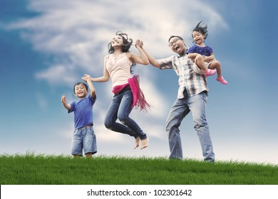 Excited and happy asian family jumping in meadow shot during summer