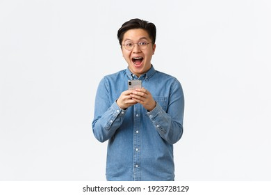 Excited happy asian man reacting cheerful at awesome news read online, holding mobile phone and looking thrilled with event coming up. Guy download cool new app or game, white background