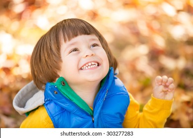 Excited happy baby enjoying autumn fall in the park