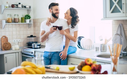 Excited happy beautiful young couple in love cooking in the kitchen and having fun together while making fresh healthy fruits salad