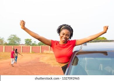 excited and happy black girl sitting out from the window of a car smiling with arms stretched