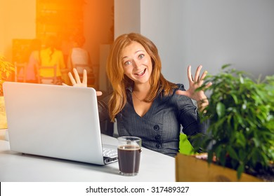 Excited happy businesswoman with raised arms sitting at the table with laptop celebrating her success. Funny image of winner or surprised office worker. Green eco office concept