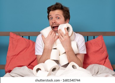 Excited happy caucasian man in bed hugging a pile of toilet paper isolated on blue background. Stay at home concept. Studio shot