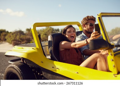 Excited happy couple enjoying road trip in their open top car. Man driving the car young woman taking a selfie from her mobile phone.