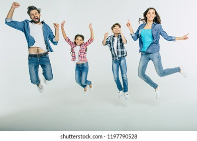 Excited and happy family in casual clothes are jumping together and shouting isolated in white