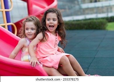 Excited happy girls on the slide