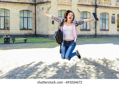 Excited happy joyful female student jumping with book in her hand and triumphing because of passing the exams