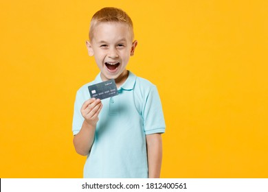 Excited happy little fun male kid boy 5-6 years old wearing stylish blue turquoise t-shirt polo hold in hand mockups of credit bank card isolated on yellow color wall background child studio portrait