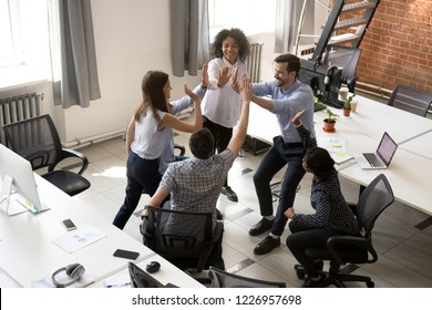 Excited happy multiracial office team giving high five celebrating victory together, business people group sharing unity, good relations, teamwork success, engaging in teambuilding concept, top view