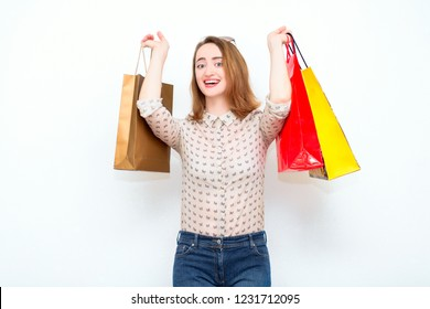 Excited and happy red-haired woman with bags after shopping is standing on a light background and smiling. The modern concept of fashion, style, shopping, discounts, sales.