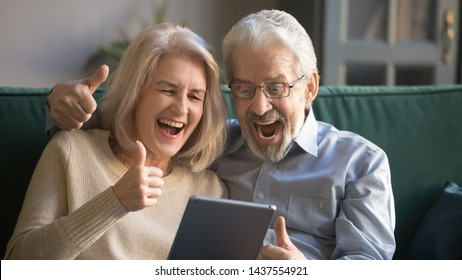 Excited happy senior couple looking at digital tablet got prize new online sale offer, overjoyed elder old winners show thumbs up celebrate lottery bid win betting success, reading good internet news
