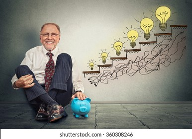 Excited happy senior executive man sitting on a floor in his office with piggy bank celebrates business success, promotion, company growth isolated on gray wall texture background