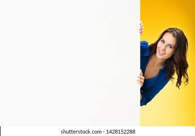 Excited happy smiling beautiful young woman holding blank billboard with copy space for ad, isolated on yellow orange  background. Business concept. Brunette model in blue confident clothing at studio