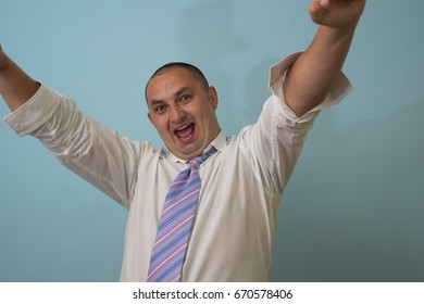Excited happy successful man triumphing with raised hands