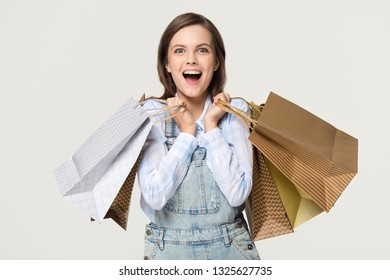Excited happy teen girl shopper holding many paper bags enjoy fashion sale, overjoyed ecstatic young woman model customer shopaholic carrying shop purchases isolated on white grey studio background
