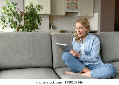 Excited happy woman with a tablet is sitting on a sofa. Pretty young caucasian woman sitting in the living room in denim clothes, holding a tablet, chatting online, browsing internet, smiling