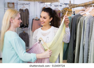 Excited happy women shopping pullover and skirt at the apparel store