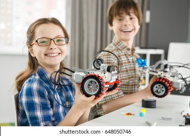 Excited and happy young cute girl smiling to the camera holding her electronic robot copyspace her brother posing with his robot on the background education learning science children creativity study