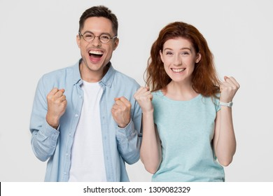 Excited happy young family couple winners celebrate win motivated by triumph rejoice victory success together, overjoyed ecstatic euphoric man and woman isolated on white grey blank studio background