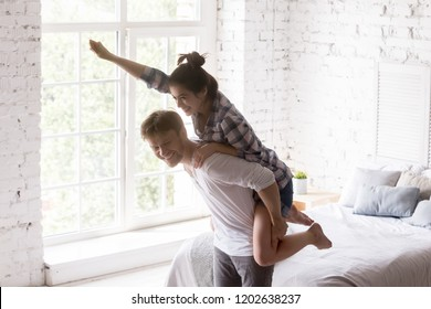 Excited happy young woman piggyback man in bedroom, loving couple having fun together at home, laughing spouses in new own apartment, looking forward to good future, husband carrying wife on his back
