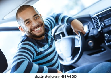As excited as he can be. Handsome African man sitting in his car smiling to the camera excitedly