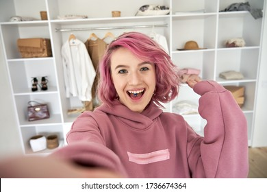 Excited hipster gen z teen girl fashion social media channel blogger stylist with pink hair piercing wear hoodie look at camera record vlog video tutorial in front of clothes wardrobe, face headshot.