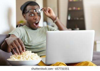 Excited hipster male with dark skin wearing casual T-shirt and hat taking off his glasses looking with bugged eyes and opened mouth into laptop while watching horrified news taking popcorn from bowl