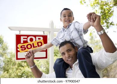 Excited Hispanic Father and Son in Front of Sold For Sale Real Estate Sign.