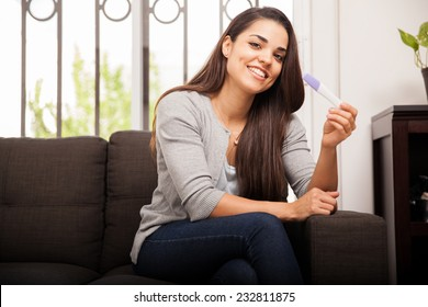Excited Hispanic young woman holding a pregnancy test and smiling