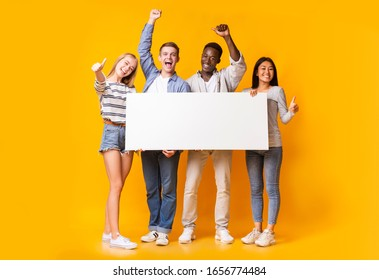 Excited international group of teenagers holding empty white plackard, yellow background