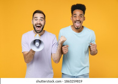 Excited joyful young friends european african american men 20s in casual violet blue t-shirts screaming in megaphone doing winner gesture isolated on bright yellow colour background studio portrait
