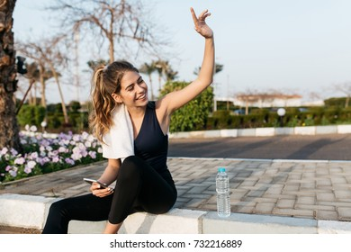 Excited joyful young woman in sportswear gratulating to side in sunny morning. Expressing positivity, sitting on street of tropical city, smiling, training, healthy lifestyle