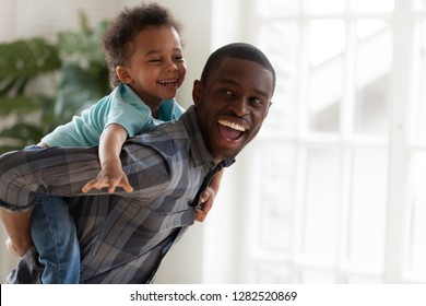 Excited kid boy playing with happy african american father at home, cheerful black dad piggybacking cute child carrying little son on back having fun on weekend spending time together with daddy