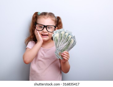 Excited kid girl earring money and thinking how spend its on blue background with empty copy space