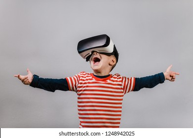 Excited kid with hands spread having fun with VR glasses. Portrait of happy child wearing virtual reality headset against grey background.