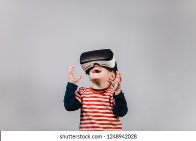 Excited kid having fun with VR glasses. Portrait of cheerful child wearing virtual reality headset against grey background.