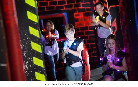 Excited kids aiming laser guns at other players during lasertag game with parents in dark room