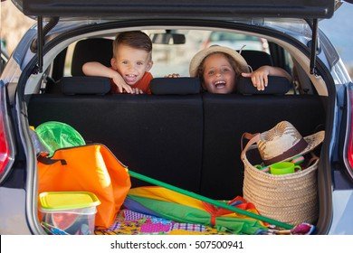excited kids in car arriving at summer vacation