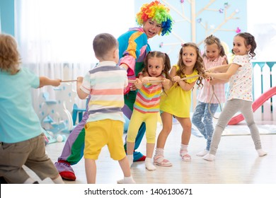 Excited kids and clown playing tug of war in club