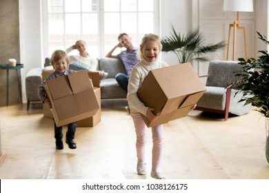 Excited kids laughing playing in new home carrying boxes, happy family with children enjoying relocation, small girl and boy having fun in living room helping parents to pack, moving day concept