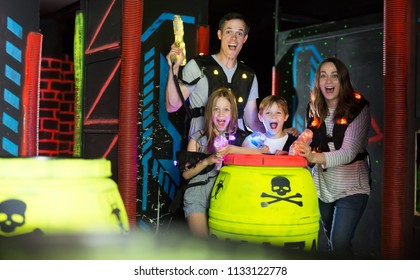 Excited kids and theirs parents aiming laser guns at other players during lasertag game in dark room