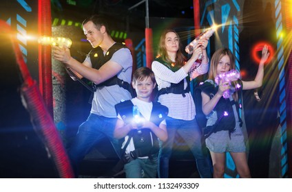 Excited kids and theirs parents in bright beams of laser guns during laser tag game in dark room