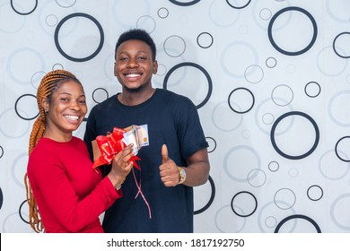 excited lady flaunting an enveloped wrapped with a ribbon containing cash gift and a guy standing next to her smiling and gives a thumbs up
